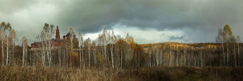 Cloudy sky above the birch grove and the Orthodox monastery Stock Photos