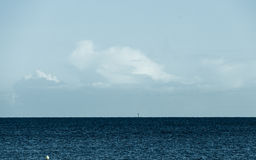 Cloudy sky above blue surface of the sea Royalty Free Stock Image