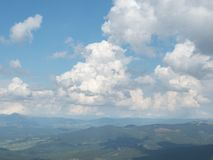 Cloudy sky above the mountain range. Carpathians mountains at summer, west Ukraine. White cumulus floating in blue sky. Green forest on hillsides. Ukrainian stock photography