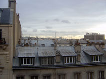 Cloudy sky above the roofs of Paris. Typical Parisian roof scape under the cloudy sky of a wintertime sunrise royalty free stock photos
