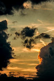 Cloudy sky with airplane exhaust pollution trails while sunset Royalty Free Stock Photos