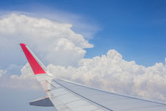 Cloudy sky and airplane wing view from window.  Stock Photo