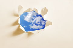 Cloudy sky behind paper hole Royalty Free Stock Image