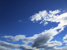 Cloudy sky. The blue sky with white cumulus clouds fantastically shaped stock photos