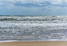 Cloudy sky and breaking waves Stock Photography