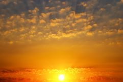 Cloudy sky and bright sunrise over the horizon. Bright sunrise over the horizon. In the blue sky, small cumulus clouds. Picturesque morning scenery royalty free stock image