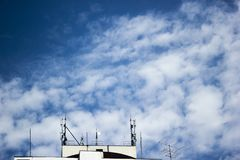 Cloudy sky with a building. A cloudy sky at daylight in a urban environment with white wall Stock Images