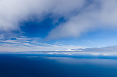 Cloudy sky and calm ocean background Stock Images