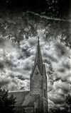 Cloudy Sky, Church Steeple on 35mm film. Church steeple clocktower framed by trees under cloudy skies, photo taken with 1952 vintage Kodak Signet 35, 35mm film Stock Photography