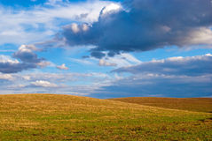 Cloudy sky and field after harvest Stock Photos