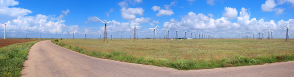 Cloudy sky and field with wind-turbines. Panorama Stock Images