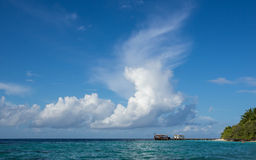 Cloudy sky, ocean and a boat near the island Royalty Free Stock Photography