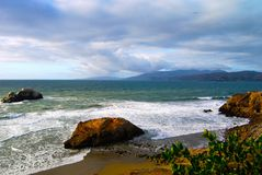 Rocky California Coast near San Francisco. Cloudy sky with ominous threat of rain turns the ocean a deep teal. Location is the Bath House Ruins on the California royalty free stock photos