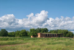 Cloudy sky over the abandoned buildings of the Russian village.  Royalty Free Stock Photos