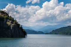 Cloudy sky over the lake, Romania. Cloudy sky over the lake with mountains in the backgroun, Romania stock images