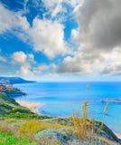 Cloudy sky over Lu Bagnu shoreline Stock Photo