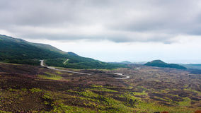 Cloudy sky over road in lava fields on Mount Etna Royalty Free Stock Photos