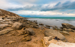 Cloudy sky over sea, rocks on coast Royalty Free Stock Images