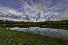 Cloudy sky over small lake in the forest Royalty Free Stock Images