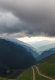 Cloudy sky over winding Transfagarasan road. Cloudy sky over famous motorcycle road - Transfagarasan, Carpathians, Romania Royalty Free Stock Images
