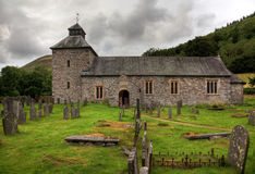 Cloudy sky overshadows Melangell Church in Wales. Threatening skies over the old stone church of Melangell stock image