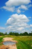 Cloudy sky and puddle on road Royalty Free Stock Images