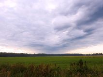 Field and clouds before rain, Lithuania Royalty Free Stock Photography