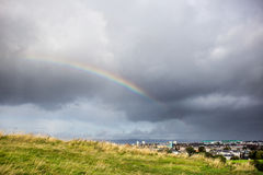 Cloudy sky and rainbow above the city Stock Images