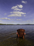 CLOUDY_SKY_RED_CHAIR. A red Adirondack chair is seen at the edge of a freshwater lake in Nova Scotia Stock Images