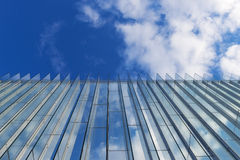 Cloudy sky reflected in the glass wall of a  modern building Stock Image