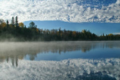 Cloudy Sky Reflecting on an Autumn Lake. Cloudy Sky Reflecting on a Misty Autumn Lake - Ontario, Canada royalty free stock photos