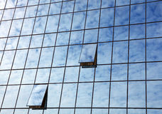Cloudy sky reflection in business building glass. Cloudy blue sky reflection in glass of office business building with open windows, low angle view Royalty Free Stock Photography
