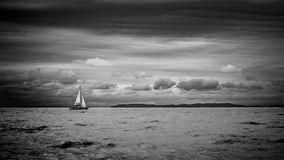 Black and white lake view with sailing boat and clouds overcast sky Stock Photos