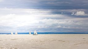 Lake landscape view with sailing boats and clouds overcast sky Royalty Free Stock Photo
