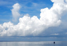 Cloudy sky and the sea. Blue cloudy sky with a boat Royalty Free Stock Photo