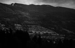 Cloudy Sky in Vancouver Black and White. Distorted film picture of northern Vancouver`s houses on the side of a mountain stock photo