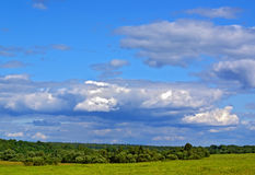 Cloudy sky view. Summer rural landscape with cloudy sky, green grass and trees Stock Images