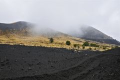 Cloudy Slopes of Mount Etna, Sicily. Black Igneous Rock of Mount Etna, Sicily Stock Photo