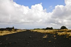Cloudy Slopes of Mount Etna, Sicily. Black Igneous Rock of Mount Etna, Sicily Royalty Free Stock Photos