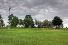 Cloudy Soccer Field. A cloudy unoccupied soccer field with trees in the background. (HDR photograph Royalty Free Stock Photos