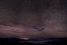 Cloudy star night. Fog, mountains and city lights far away. Night panorama of highest Ukrainian peaks royalty free stock image