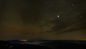 Cloudy starry sky over foggy mountains Royalty Free Stock Photos