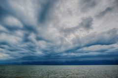Cloudy storm in the sea before rainy. Tornado storms cloud above the sea. Monsoon season. Huge storm clouds with rain over sea , Strong winds, heavy rain storm Stock Photo