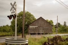 Cloudy summer day with road/highway barn and railroad crossing stock image