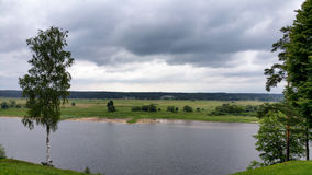 Cloudy summer landscape with river stock photo