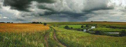 Cloudy summer panoramic landscape with dirt country road,fields,meadows,woods and small river. stock photography