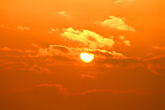 Cloudy sun. Beautiful orange sun covered by small clouds Stock Images
