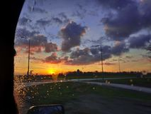 A cloudy sunrise with beautiful colors captured through the window of a car with rain droplets on it. orange sky. blue clouds. royalty free stock photography