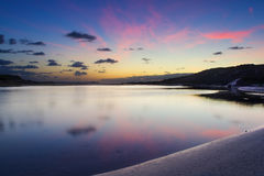 Cloudy sunrise over a quiet lagoon with cloud patterns reflected Stock Photo
