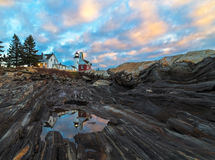 Cloudy sunrise at Pemaquid Point, Maine. This is a cloudy sunrise at Pemaquid Point in Bristol, Maine.  A reflection of the lighthouse can be seen in a puddle Royalty Free Stock Photo